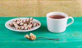 Чай в чашке и tubules вафли в плите Стоковая Фотография RF