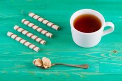 Чай в чашке и tubules вафли в плите Стоковое Фото