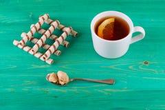 Чай в чашке и tubules вафли в плите Стоковая Фотография