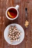 Чай в чашке и tubules вафли в плите Стоковые Фото