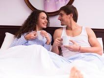 Чай Гая и девушки выпивая и беседовать в кровати Стоковое фото RF