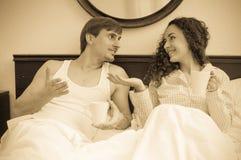 Чай Гая и девушки выпивая и беседовать в кровати Стоковые Изображения