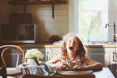 Чай девушки ребенка выпивая для завтрака в кухне страны лета стоковое фото rf