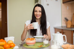 Чай девушки брюнет выпивая в moring в кухне стоковая фотография rf