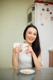 Чай девушки выпивая с печеньем в утре Стоковая Фотография RF