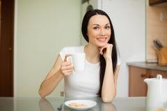 Чай девушки выпивая с печеньем в утре Стоковые Изображения RF