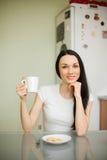 Чай девушки выпивая с печеньем в утре Стоковое Фото