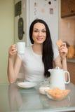 Чай девушки выпивая с печеньем в moring Стоковые Изображения