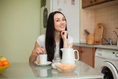 Чай девушки выпивая с печеньем в moring стоковая фотография
