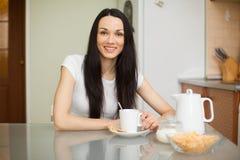 Чай девушки выпивая с печеньем в moring стоковые фотографии rf