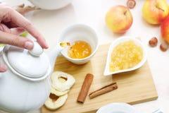 Чай Женщина льет чай в чашку стоковые изображения