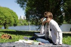Чай женщины выпивая на пикнике стоковое фото
