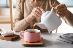 Чай женщины лить в керамическую чашку на таблице, стоковое изображение