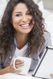 Чай или кофе женщины выпивая на компьютере таблетки Стоковые Фотографии RF