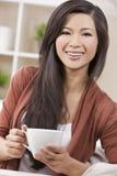 Чай или кофе красивейшей востоковедной женщины выпивая Стоковые Изображения RF