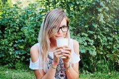 Чай Чай или кофе красивейшей девушки выпивая Здоровое питье Женщина с чашкой над предпосылкой зеленого цвета природы Стоковое Изображение RF