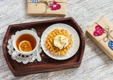 Чай лимона, waffles с мороженым, мед и гайки в винтажном подносе, домодельные подарки дня валентинки в бумаге kraft Стоковые Изображения RF