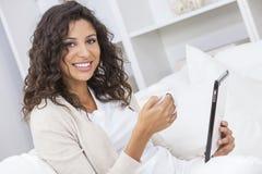 Чай или кофе женщины выпивая используя планшет Стоковое Фото