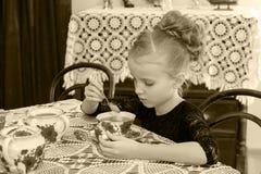 Чай красивой маленькой девочки выпивая на таблице Стоковые Изображения