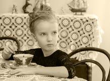 Чай красивой маленькой девочки выпивая на таблице Стоковое Изображение