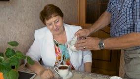 Чай красивых пожилых пар выпивая на таблице видеоматериал