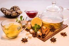 Чай лимона в прозрачной кружке около винзавода варенья поленики, мяты и имбиря стеклянных и печений шоколада на плите на bacgro w Стоковое фото RF