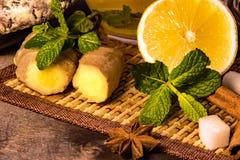 Чай лимона в прозрачных печеньях имбиря мяты кружки и винзавода и шоколада cinnamo на лимоне черной плиты Стоковые Изображения