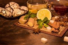 Чай лимона с прозрачными кружкой и чайником варенье мяты и поленики, винзавод стекла имбиря и cinnamo и печенья шоколада на bl Стоковое Изображение
