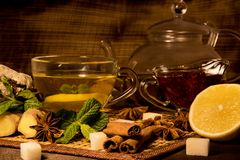 Чай лимона с прозрачными кружкой и чайником варенье мяты и поленики, винзавод стекла имбиря и cinnamo и печенья шоколада на bl Стоковое Фото