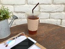 Чай льда в пластичных стеклах, стеклах, smartphones и документах на деревянной таблице рядом с белой стеной с концепцией relaxin Стоковое фото RF