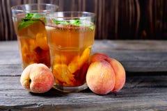 Чай льда персика в стекле с мятой на деревянном столе Стоковое Изображение RF
