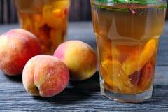 Чай льда персика в стекле с мятой на деревянном столе Стоковая Фотография RF