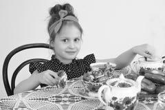 Чай маленькой девочки выпивая на таблице Стоковые Фото