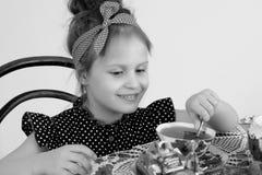 Чай маленькой девочки выпивая на таблице Стоковые Изображения RF