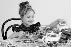 Чай маленькой девочки выпивая на таблице Стоковое Изображение