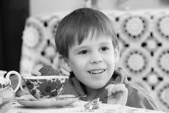 Чай мальчика выпивая на таблице Стоковые Изображения