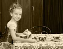 Чай милой маленькой девочки выпивая на старой таблице Стоковое фото RF
