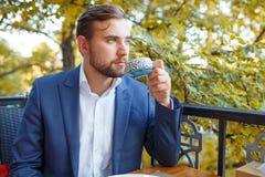 Чай молодого человека выпивая с помадками на запачканной естественной предпосылке Стоковая Фотография