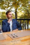 Чай молодого человека выпивая с помадками на запачканной естественной предпосылке Стоковое Фото