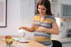 Чай молодой беременной женщины лить в чашку на таблице стоковые фото