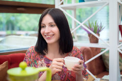 Чай молодой женщины выпивая в кафе Стоковые Фотографии RF