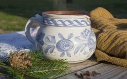 Чай натюрморта зимы горячий куря в деревенской белой сини покрасил керамическую чашку с бежевым шерстяным шарфом, елевыми ветвями стоковые фото