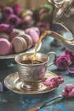 Чай от чайника льет внутри чашку против с печений миндалины Китайский чай от Юньнань Bi Lo Chun Селективный фокус Стоковая Фотография RF