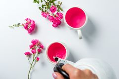 Чай персоны лить с розовыми цветками на таблице стоковое изображение
