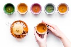 чай питья Вручите чашку владением около бака чая на белом взгляд сверху предпосылки Стоковое фото RF