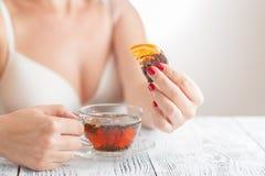 Чай питья женщины на спальне с помадками Стоковая Фотография RF