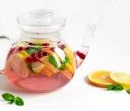 Чай плода с апельсином, лимоном и клюквами Чайник с апельсином плода, лимоном, клюквой, мятой Чай для холодов витамин типа помера стоковые фото