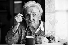 Чай пожилой женщины выпивая сидя на таблице Стоковое Изображение RF