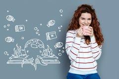 Чай положительной женщины выпивая и усмехаться пока думающ о подводной жизни Стоковые Фото