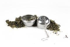 Чай разбросан на белую предпосылку с стрейнером для заваривать Стоковое фото RF